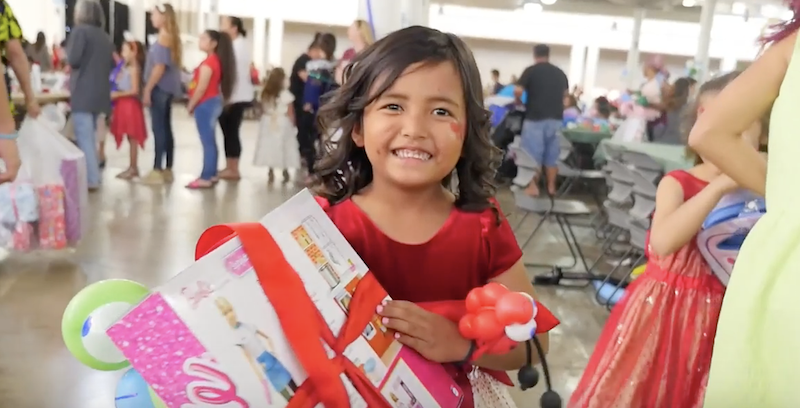 Girl happily holds gift from Santa at 19th Annual Holiday Party for children in foster care, Family Programs Hawaii